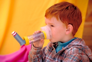 Young red haired child using an inhaler with a nebulizer