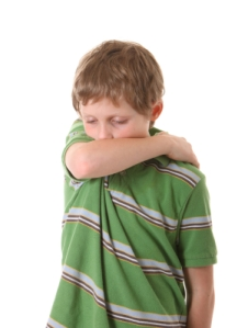boy coughing into arm