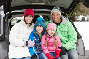 Family Sitting In Boot Of Car Wearing Winter Clothes