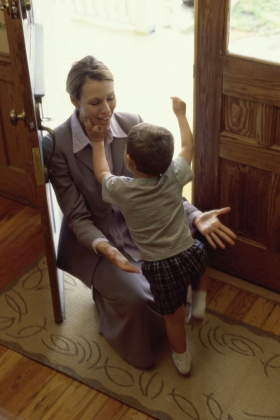 Little boy greeting his mother at the front door