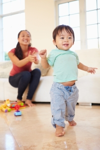 One Year Old Boy Taking First Steps With Mother