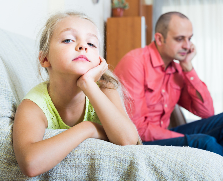 Unhappy small girl having conflict with father at home