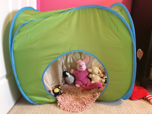 A child's tent filled with pillows and stuffed animals