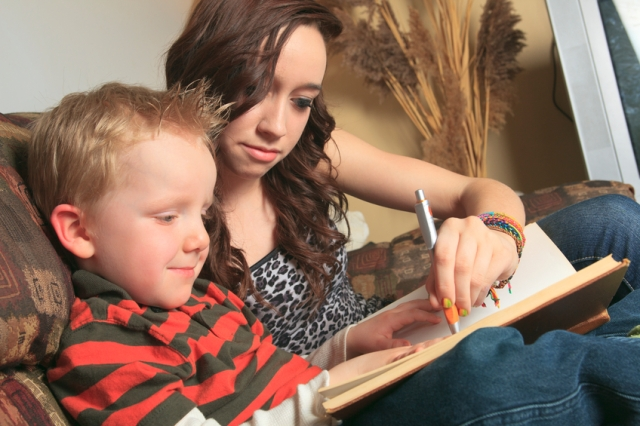 Babysitter and little boy write in book together