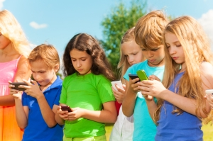Group of busy kids looking at their phones texting sms and playing staying outside