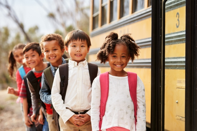 Elementary school kids queueing to get on to a school bus