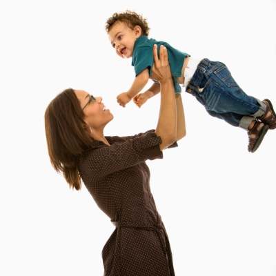 Side view of mid adult African American mom lifting happy toddler son into air above head.