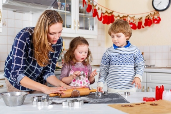 Happy family baking Christmas cookies at home. Little boy, girl and mother having fun in domestic decorated kitchen. Traditional leisure with kids on Xmas