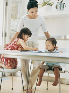 Mother Helping Her Son and Daughter With Their Colouring In Books at the Kitchen Table