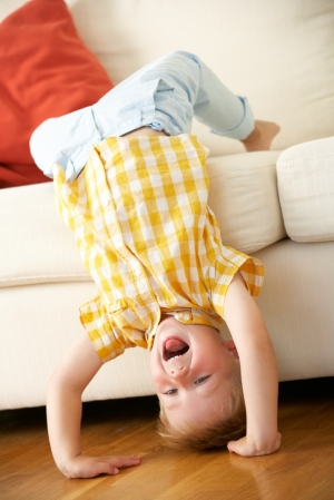 Silly toddler boy upside down hanging off couch