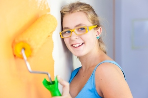 happy young woman painting a wall in her room/ colorful life / real view