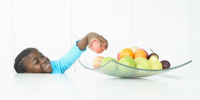 girl reaching for fruit