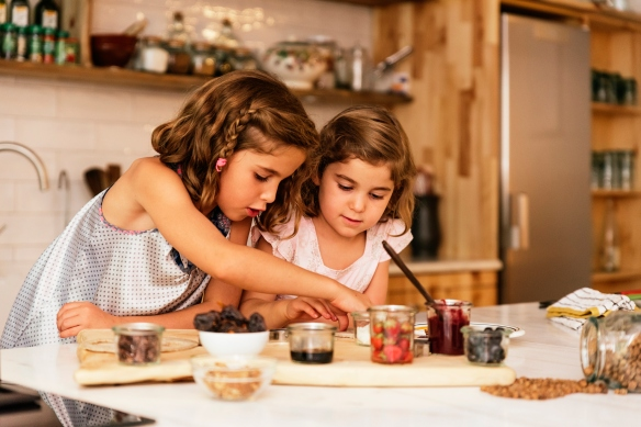 Little sisters preparing food with nuts and fruit