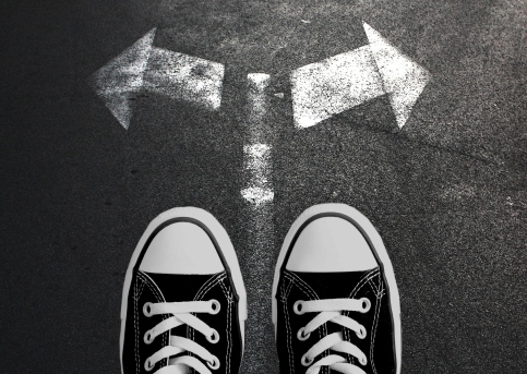 Making decisions concept. Sneakers on the asphalt road with drawn arrows pointing to two directions.