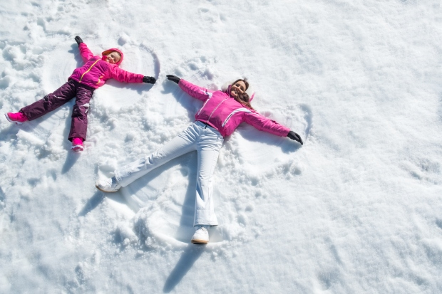 Mother and daughter happily making snow angels in the snow