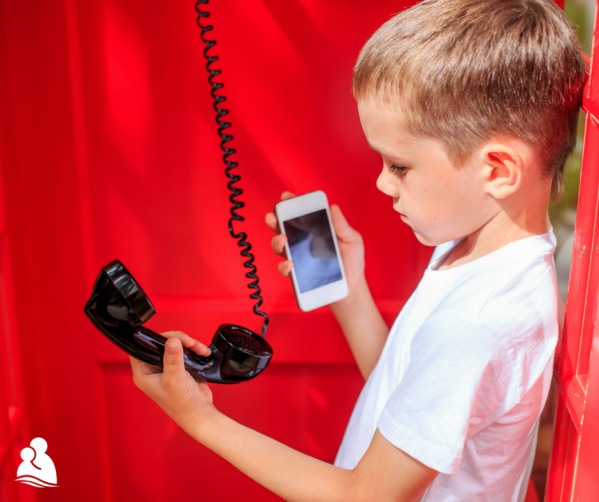 Boy in phone booth holding landline corded phone and cell phone to compare