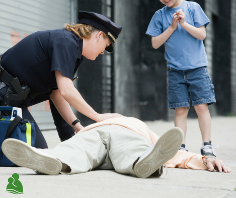 Person laying on ground with police officer looking over and young boy standing