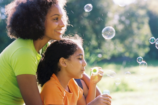 Content Mother and daughter blowing bubbles
