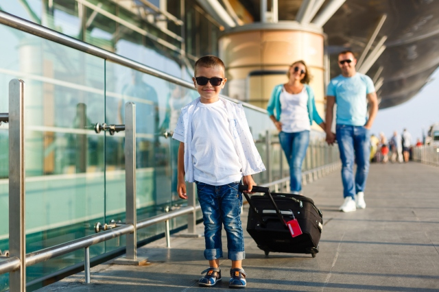 Cute little kid boy with suitcase on international airport. Mother and daughter on background, happy family waiting for flight and going on vacations.