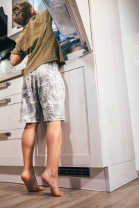 Boy reaching into fridge