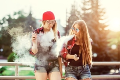 Two women vaping outdoor. The evening sunset over the city. Toned image