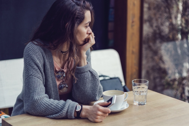 Woman sitting alone, deep in thought, having coffee and holding her mobile phone