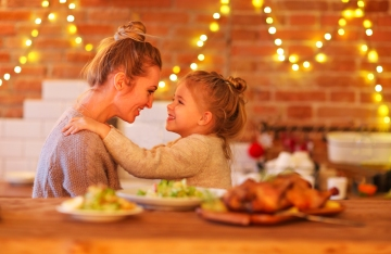 Mother and daughter enjoying healthy meal with white lights in background.