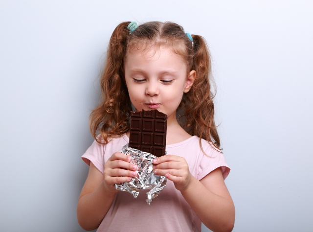 Four year old girl eating large chocolate bar with pleasure
