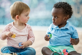 Toddlers staring at each other each holding blocks