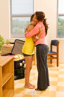 Mom hugging daughter goodbye in dorm room