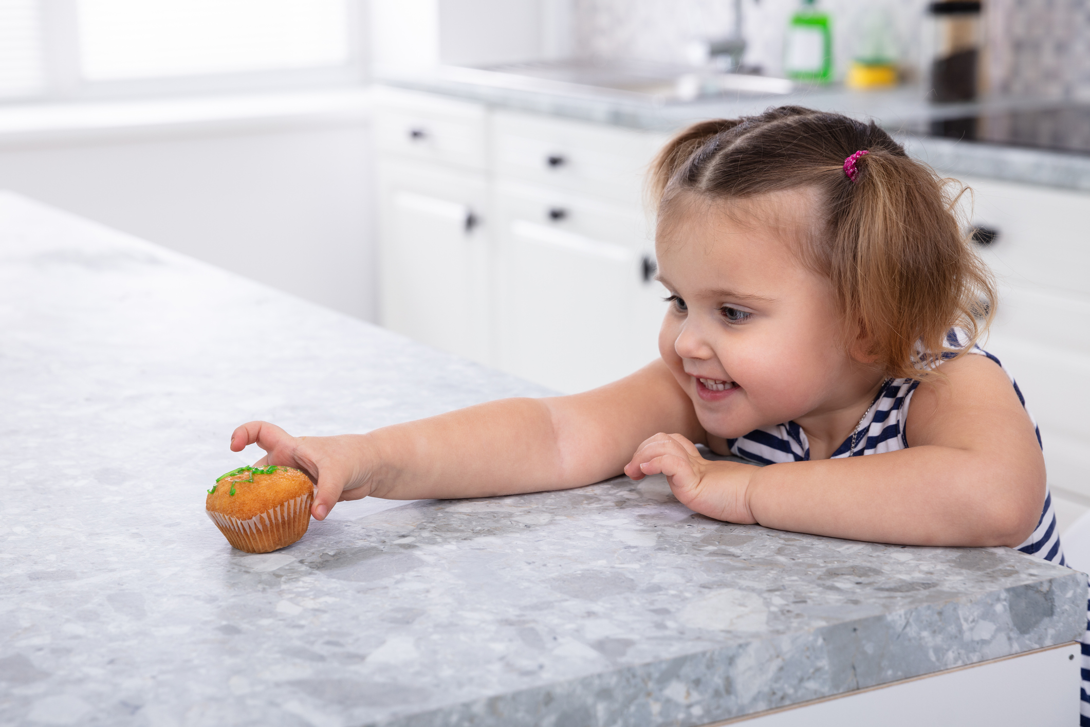 Girl's Hand Reaching For Cupcake On Kitchen Counter