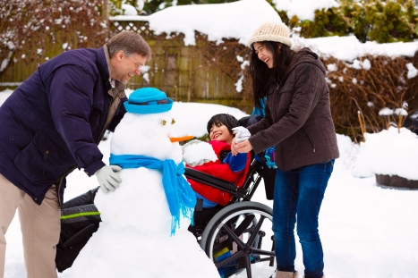 dad and 2 kids, one in wheelchair with snowman