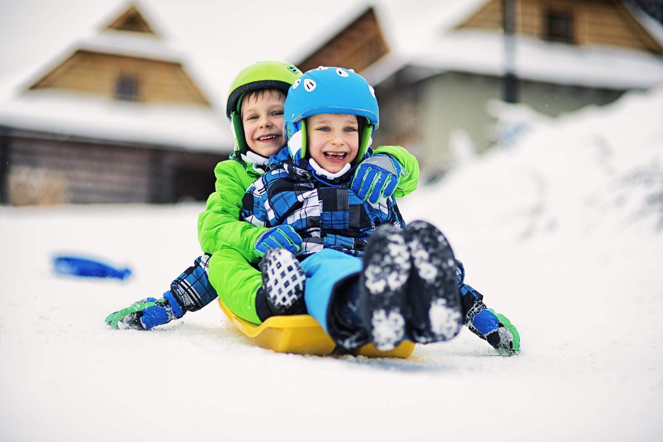 Little boys sliding on sled in winter with helmets