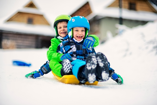 Little boys sliding on sled in winter with helmets