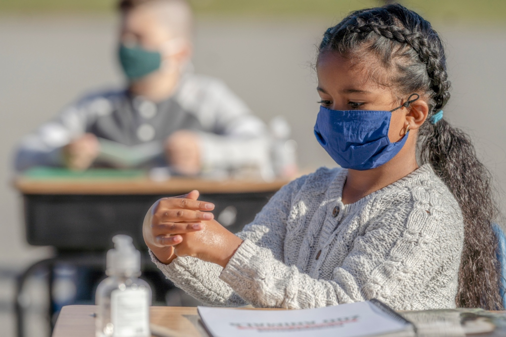 Eight year old female student sitting at classroom desk wearing a mask and applying hand sanitizer.