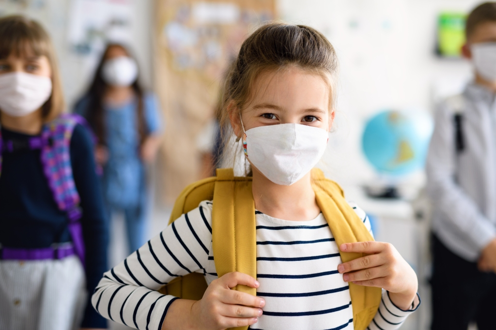Seven year old girl at school wearing backpack and face mask with other students spread out in background.