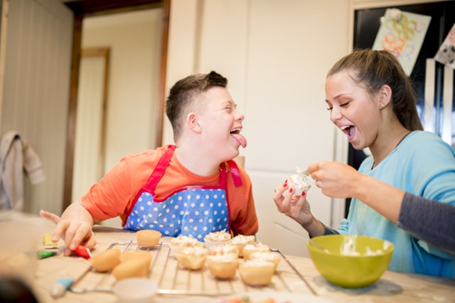 Brother and sister laughing and baking cupcakes in kitchen