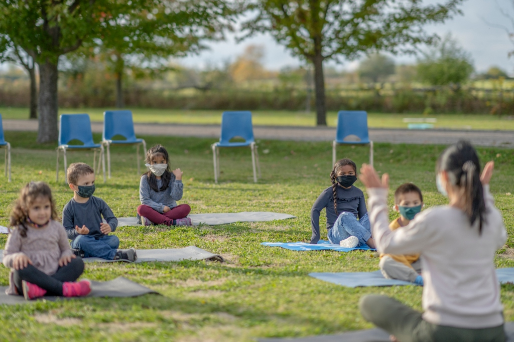 Outdoor classroom with 5 students spread out sitting on individual mats looking at teacher.