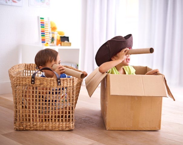 Two preschool boys each sitting in a bin pretending to be pirates each holding a paper towel roll to eye.